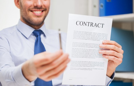 people, business and paperwork concept - close up of smiling businessman holding contract document