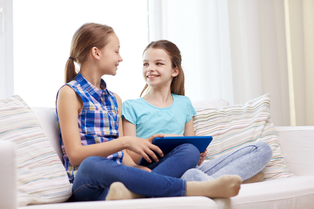 people, children, technology, friends and friendship concept - happy little girls with tablet pc computer sitting on sofa and talking at home