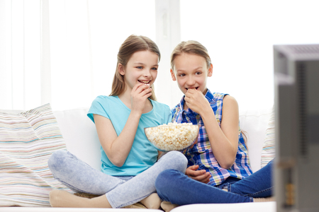 teenagers having fun: people, children, television, friends and friendship concept - two happy little girls watching tv and eating popcorn at home Stock Photo