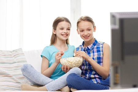 two children: people, children, television, friends and friendship concept - two happy little girls watching comedy movie on tv and eating popcorn at home Stock Photo