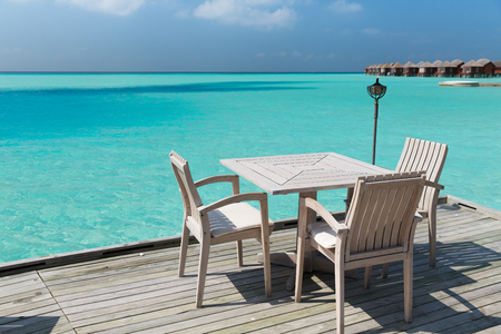 travel, tourism, vacation and summer holidays concept - outdoor restaurant wooden terrace with table and chairs over sea background