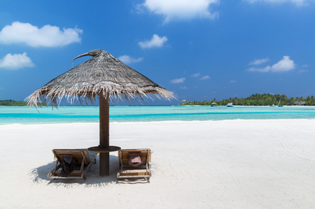 daybed: travel, tourism, vacation and summer holidays concept - palapa and sunbeds over sea and sky on maldives beach