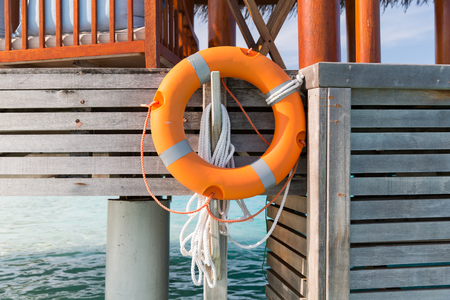 travel, tourism, safety, vacation and summer holidays concept - lifebuoy hanging on beach patio or terrace in sea water Stock Photo