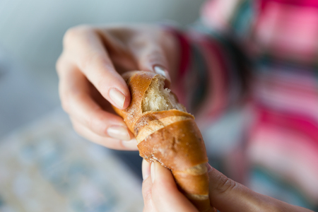 comiendo pan: alimentos, el bicarbonato, la gente y el concepto de alimentación poco saludable - Cierre de manos de la mujer con el bollo o pan de trigo