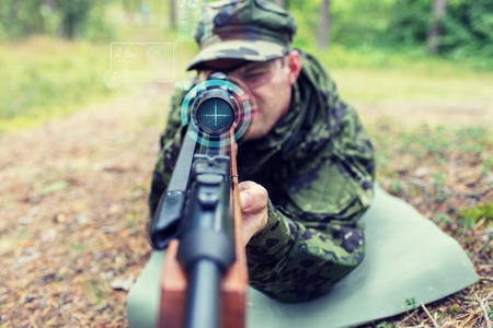 corps: hunting, war, army, technology and people concept - close up of young soldier or sniper holding gun with virtual screen projection and aiming in forest