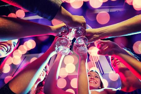 Party, Urlaub, Feiern, Nachtleben und Menschen Konzept - lächelnde Freunde mit einem Glas Sekt im Club