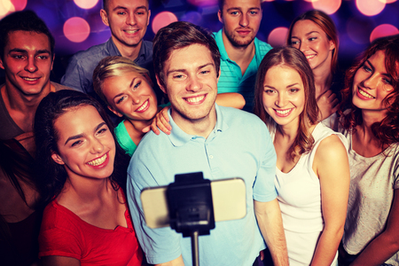 night stick: party, technology, nightlife and people concept - smiling friends with smartphone and monopod taking selfie in club