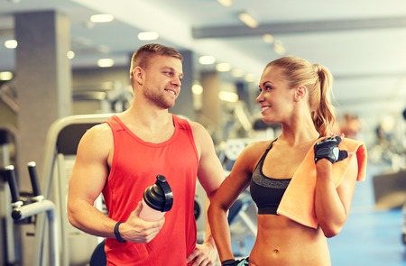 shake: sport, fitness, lifestyle and people concept - smiling man and woman with protein shake bottle and towel talking in gym