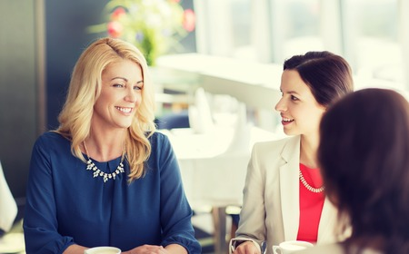 chatting: people, communication and lifestyle concept - happy women drinking coffee and talking at restaurant Stock Photo