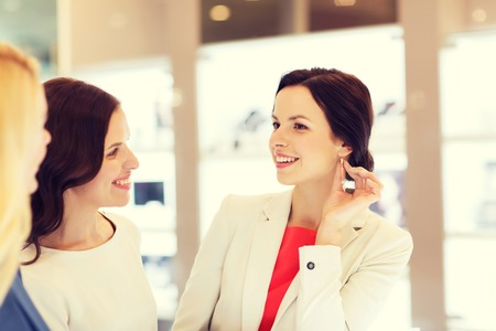 buyers: sale, consumerism, shopping and people concept - happy happy women choosing and trying on earrings at jewelry store Stock Photo