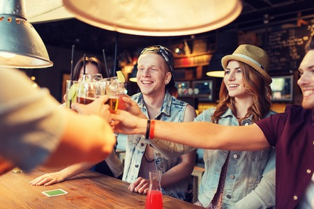 clinking: people, leisure, celebration and party concept - group of happy smiling friends clinking glasses with drinks at bar or pub