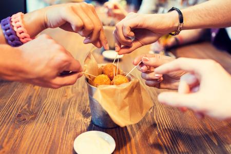 패스트 푸드, 정크 푸드, 건강에 해로운 식습관 및 요리 개념 - 가까이 막대 또는 레스토랑에서 꼬치와 치즈 공을 복용하는 사람들의 손에 스톡 콘텐츠