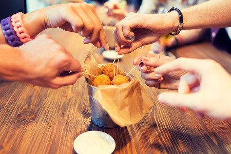fast food, junk food, unhealthy eating and culinary concept - close up of people hands taking cheese balls with skewers at bar or restaurant Stock Photo
