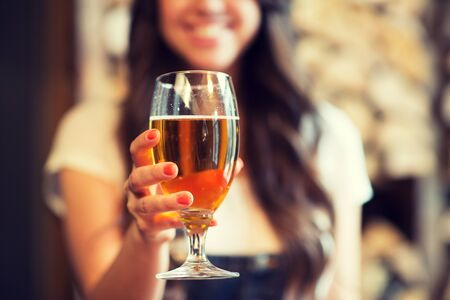 degustating: leisure, drinks, degustation, people and holidays concept - close up of smiling woman hand holding glass of draft lager beer Stock Photo