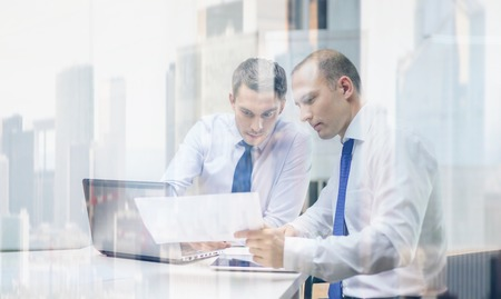 strategy meeting: business, technology and office concept - two businessmen with laptop, tablet pc computer and papers having discussion in office Stock Photo