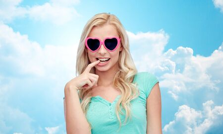 and guessing: emotions, expressions, summer and people concept - smiling young woman or teenage girl in heart shape sunglasses over blue sky and clouds background