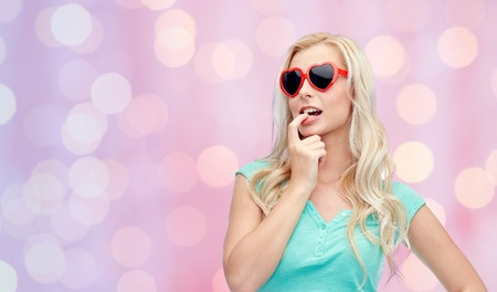 emotions, expressions, summer and people concept - smiling young woman or teenage girl in sunglasses over pink holidays lights background Stock Photo