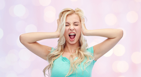 emotions, expressions, stress and people concept - young woman holding to her head and screaming over pink holidays lights background