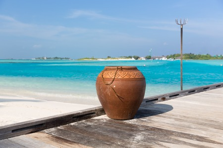 paradise bay: travel, tourism, vacation and summer holidays concept - maldives island beach with vase on wood flooring