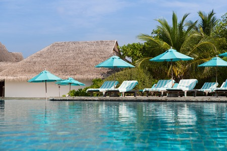 daybed: travel, tourism, vacation and summer holidays concept - parasol and sunbeds over sea and sky on maldives beach