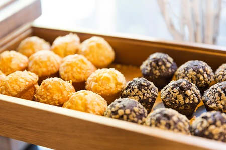 sweetstuff: food, junk-food, culinary, baking and eating concept - close up of sweets or muffins on wooden tray or box
