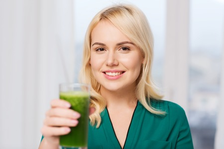jugo verde: healthy eating, vegetarian food, diet, detox and people concept - smiling young woman drinking green vegetable juice or smoothie from glass at home Foto de archivo