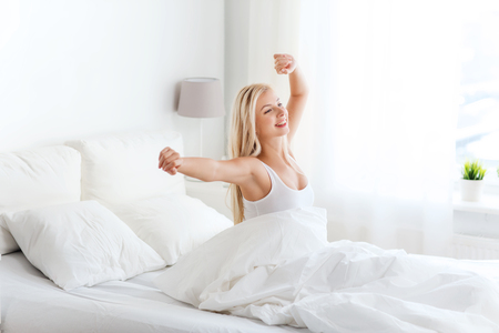 view of a comfortable bedroom: rest, sleeping, comfort and people concept - happy young woman stretching in bed after waking up at home bedroom