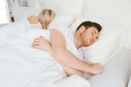 lovers quarrel: people, relationship difficulties, conflict and family concept - couple sleeping back to back in bed at home Stock Photo