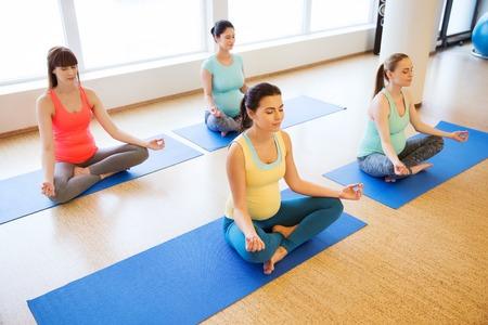 임신, 스포츠, 피트 니스, 사람들 및 건강 한 라이프 스타일 개념 - 요가 운동을 하 고 체육관에서 로터스 포즈에서 명상하는 행복 한 임신 여자의 그룹