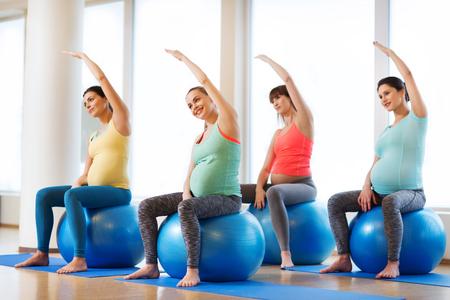 妊娠、スポーツ、フィットネス、人々、健康的なライフ スタイル コンセプト - ジムでボール運動幸せな妊娠中の女性のグループ 写真素材