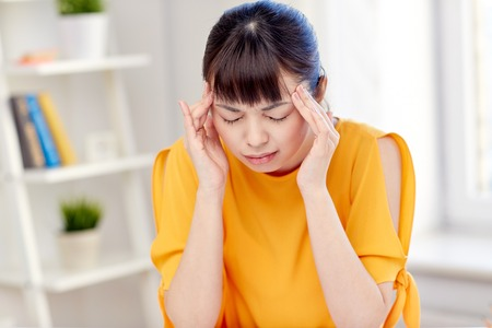 megrim: people, healthcare, stress and problem concept - unhappy asian young woman suffering from headache at home