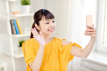 HI: people, technology and leisure concept - happy young asian woman taking selfie on smartphone at home and waving hand