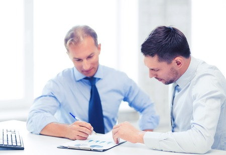 business finance: businesss concept - two businessmen discussing graphs on meeting