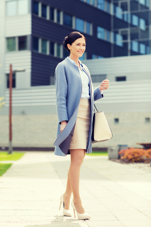 business and people concept - young smiling businesswoman over office building Reklamní fotografie