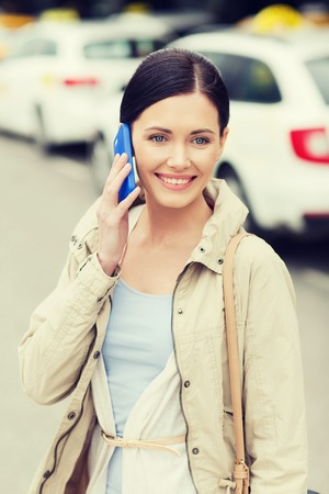 trip over: travel, business trip, people and tourism concept - smiling young woman calling and talking on smartphone over taxi station or city street
