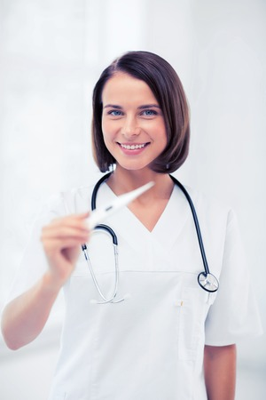 healthcare and medical - female doctor with thermometer and stethoscope.