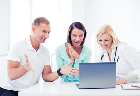 patients: healthcare, medical and technology - doctor with patients looking at laptop