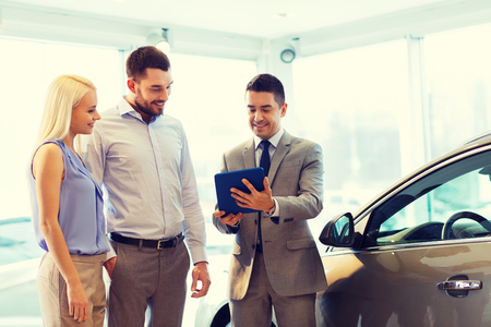 automobile: auto business, car sale, technology and people concept - happy couple with car dealer in auto show or salon