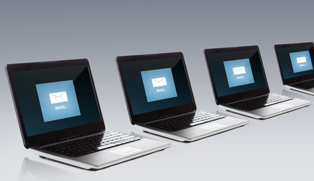 computers office: technology, internet and communication concept - laptop computers with e-mail message icon on screen