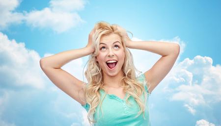감정, 표현, 헤어 스타일 및 사람들이 개념 - 웃는 젊은 여자 또는 10 대 소녀가 그녀의 머리에 들고 또는 푸른 하늘과 구름 배경 위에 머리를 만지고