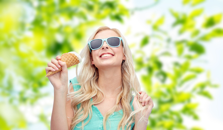 carelessness: summer, junk food and people concept - young woman or teenage girl in sunglasses eating ice cream over green natural background