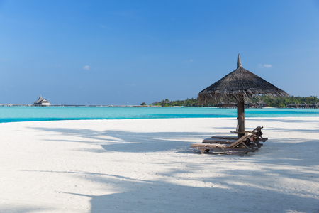 palapa: travel, tourism, vacation and summer holidays concept - palapa and sunbeds over sea and sky on maldives beach
