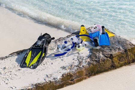 subsea: diving, snorkeling, leisure and summer vacations concept - scubas, masks and flippers on beach