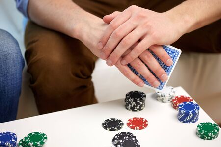 games hand: leisure, games, friendship, gambling and entertainment - close up of male hand with playing cards and chips at home