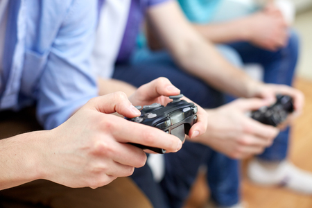 friendship, technology, games and home concept - close up of male friends playing video games at home