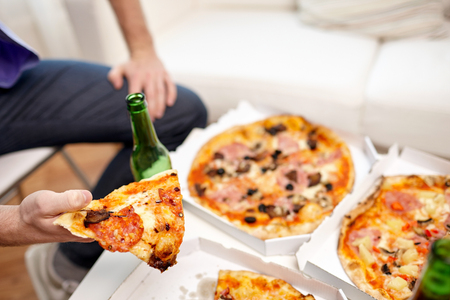 nonalcoholic beer: friendship, alcohol, people, celebration and holidays concept - close up of man drinking beer and eating pizza at home Stock Photo