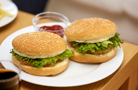eating fast food: fast food and unhealthy eating concept - close up of hamburgers on table with ketchup at fast food restaurant or home Stock Photo