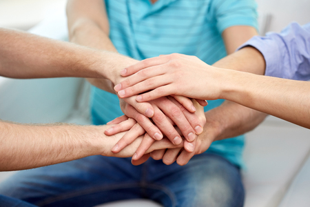 teamwork, friendship, unity, cooperation and gesture concept - close up of friends holding hands on top of each other Stock Photo