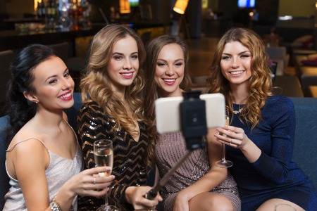 night stick: celebration, friends, bachelorette party, technology and holidays concept - happy women with champagne and smartphone selfie stick taking picture at night club