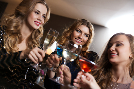 cocktail bar: celebration, friends, bachelorette party and holidays concept - happy women drinking champagne and cocktails at night club bar
